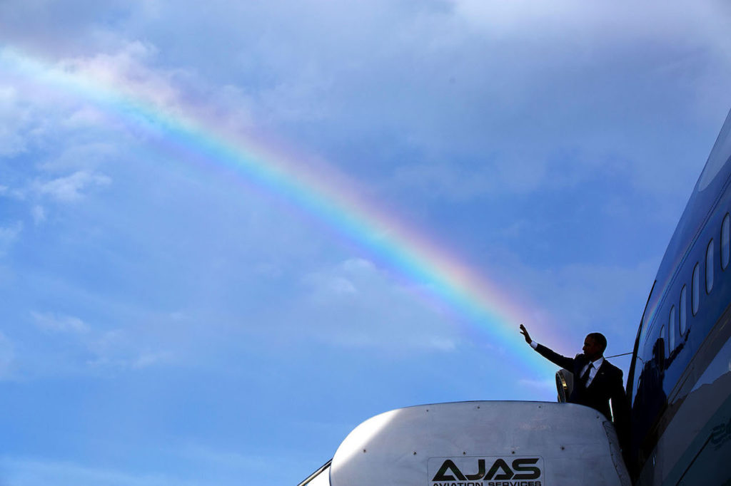 "April 9, 2015 ""The President's wave aligns with a rainbow as he boards Air Force One at Norman Manley International Airport prior to departure from Kingston, Jamaica. Read my Behind The Lens account of this photograph: http://bit.ly/1NMjCjHtk ."" (Official White House Photo by Pete Souza) This official White House photograph is being made available only for publication by news organizations and/or for personal use printing by the subject(s) of the photograph. The photograph may not be manipulated in any way and may not be used in commercial or political materials, advertisements, emails, products, promotions that in any way suggests approval or endorsement of the President, the First Family, or the White House."